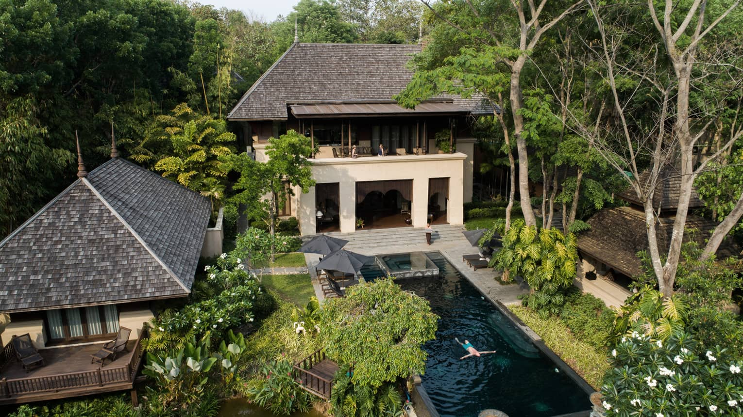 View over large villa exterior, outdoor swimming pool where man floats in water