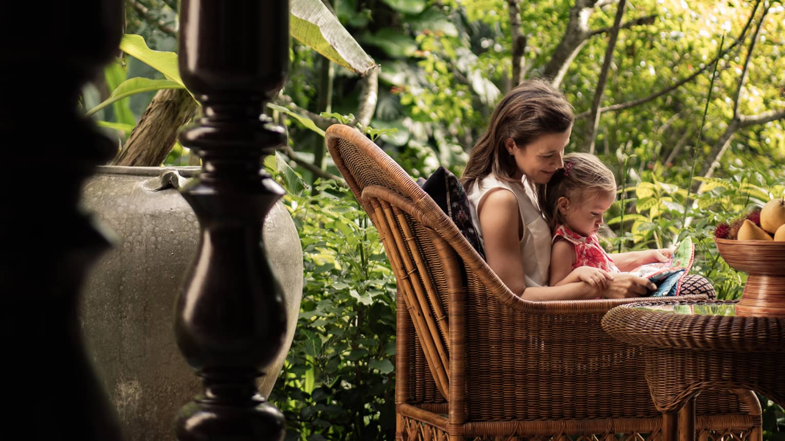 Woman read to young girl on her lap in large wicker armchair on patio by trees