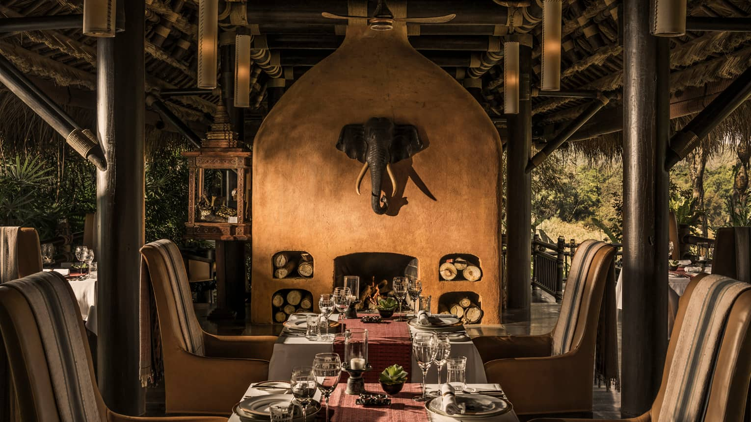 Dining tables in front of tall clay fireplace with mounted elephant head statue