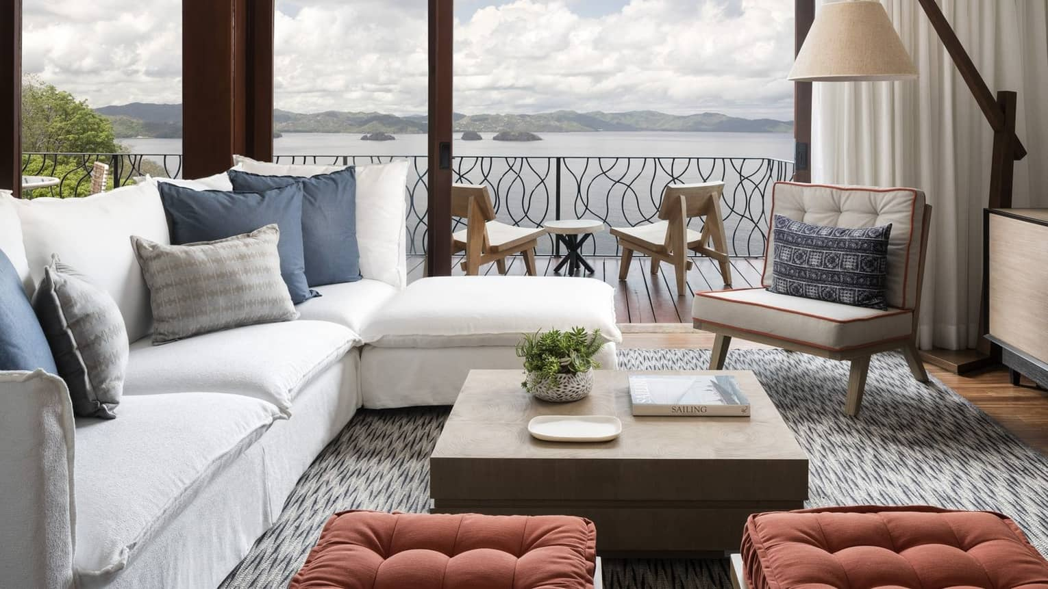 Canopy Premier Plunge Pool Suite L-shaped white sofa in front of picture windows, balcony overlooking ocean