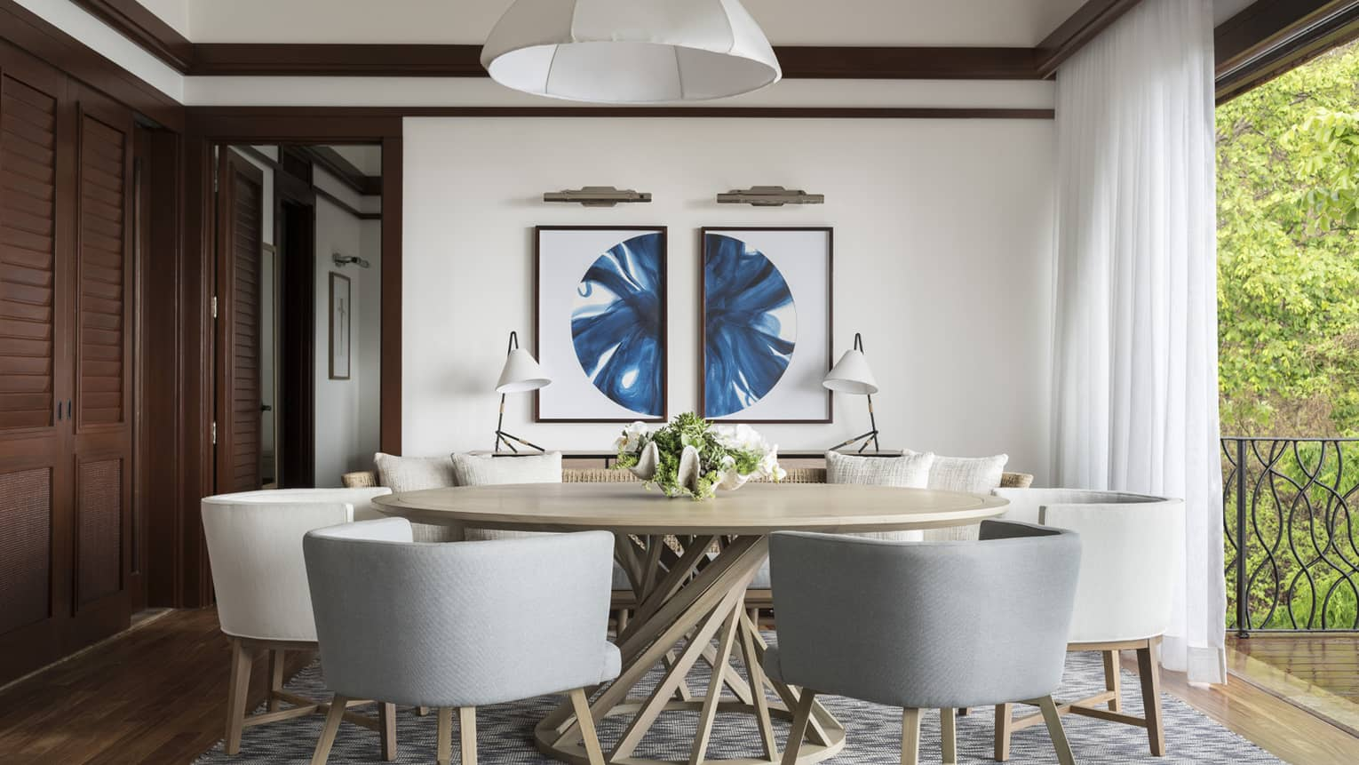Grey and white mid-century style dining chairs and round dining table by floor-to-ceiling window