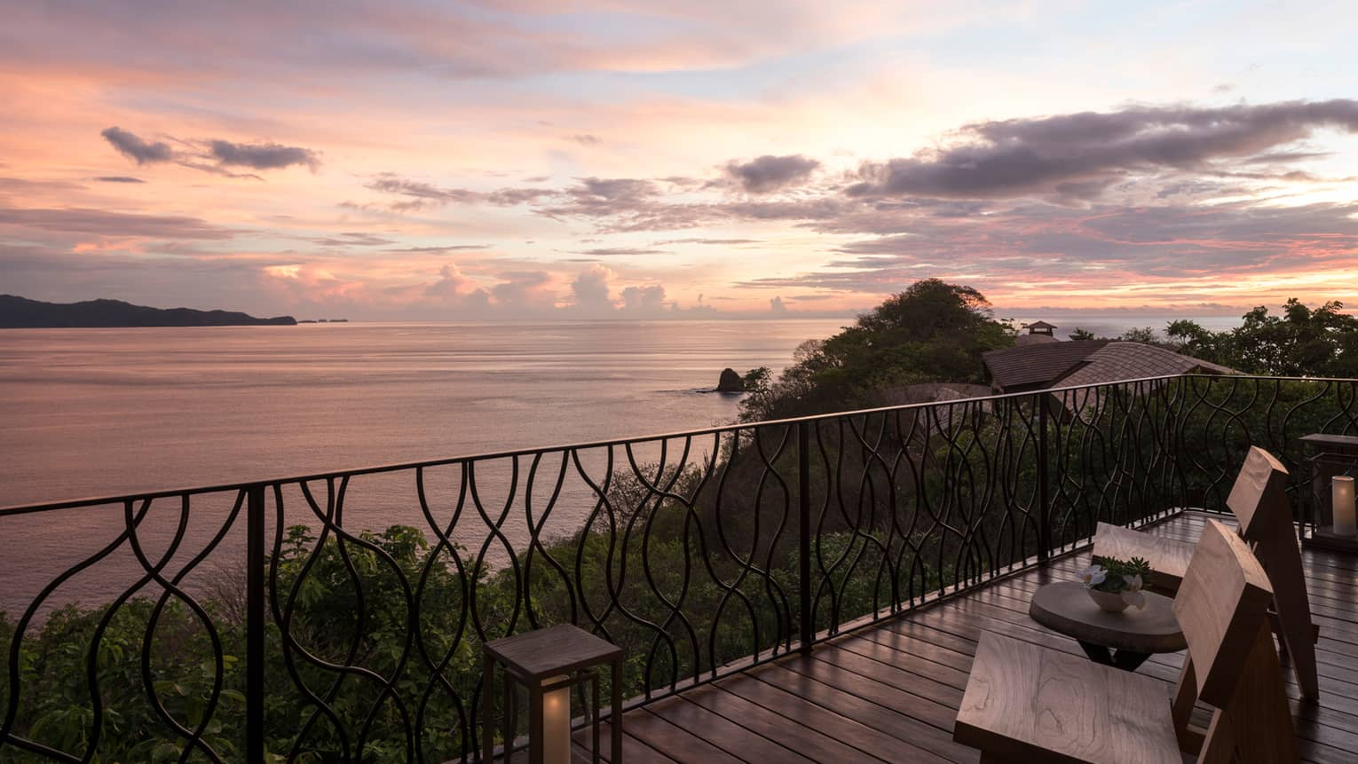 Patio chairs on wood deck with iron balcony at sunset, high above trees and ocean