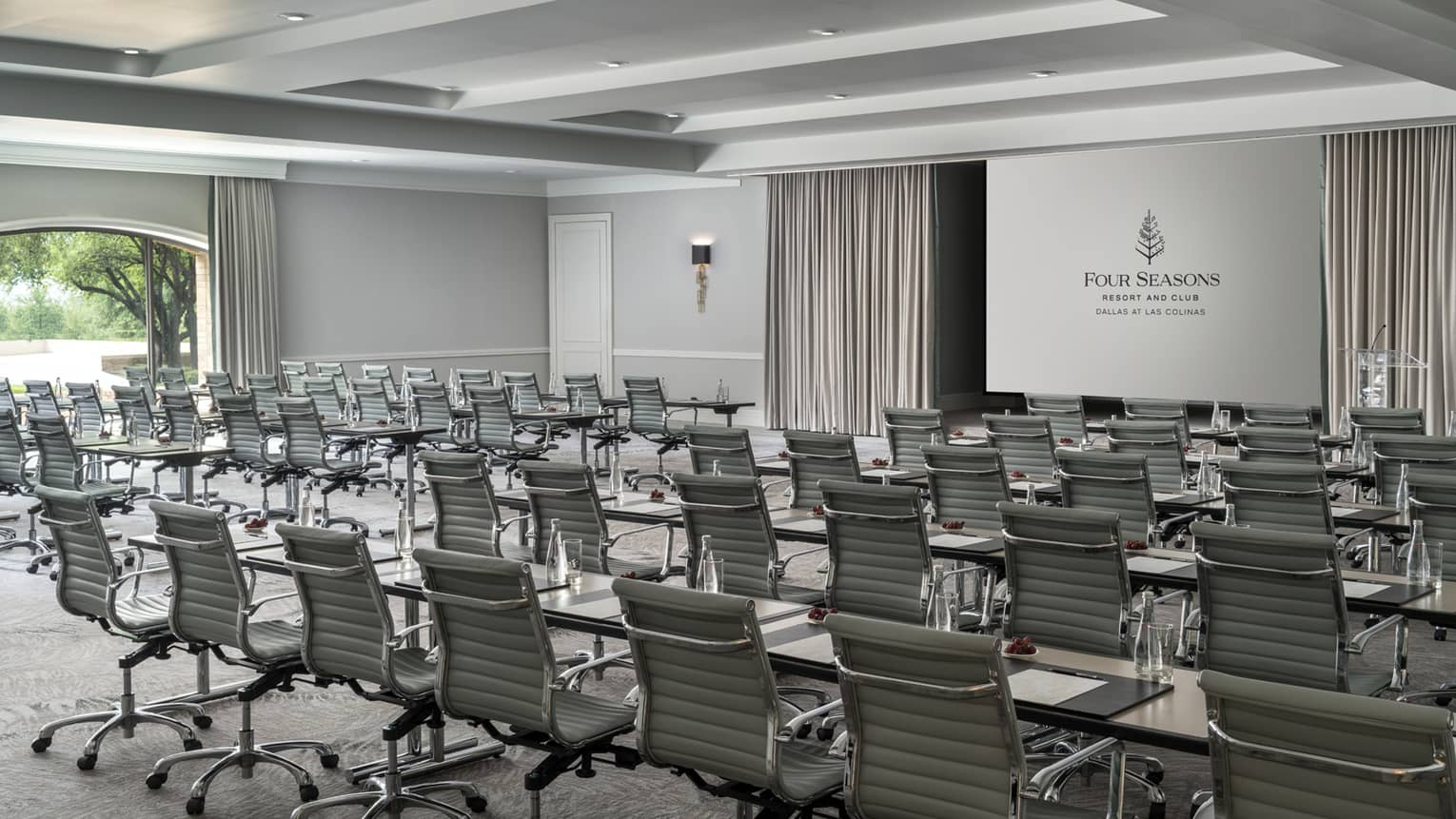 Rows of leather executive swivel chairs at long tables facing screen in large meeting room