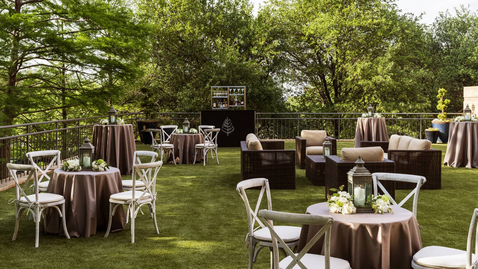 Small banquet tables, chairs on green lawn surrounded by trees in The Terrace Upper event space
