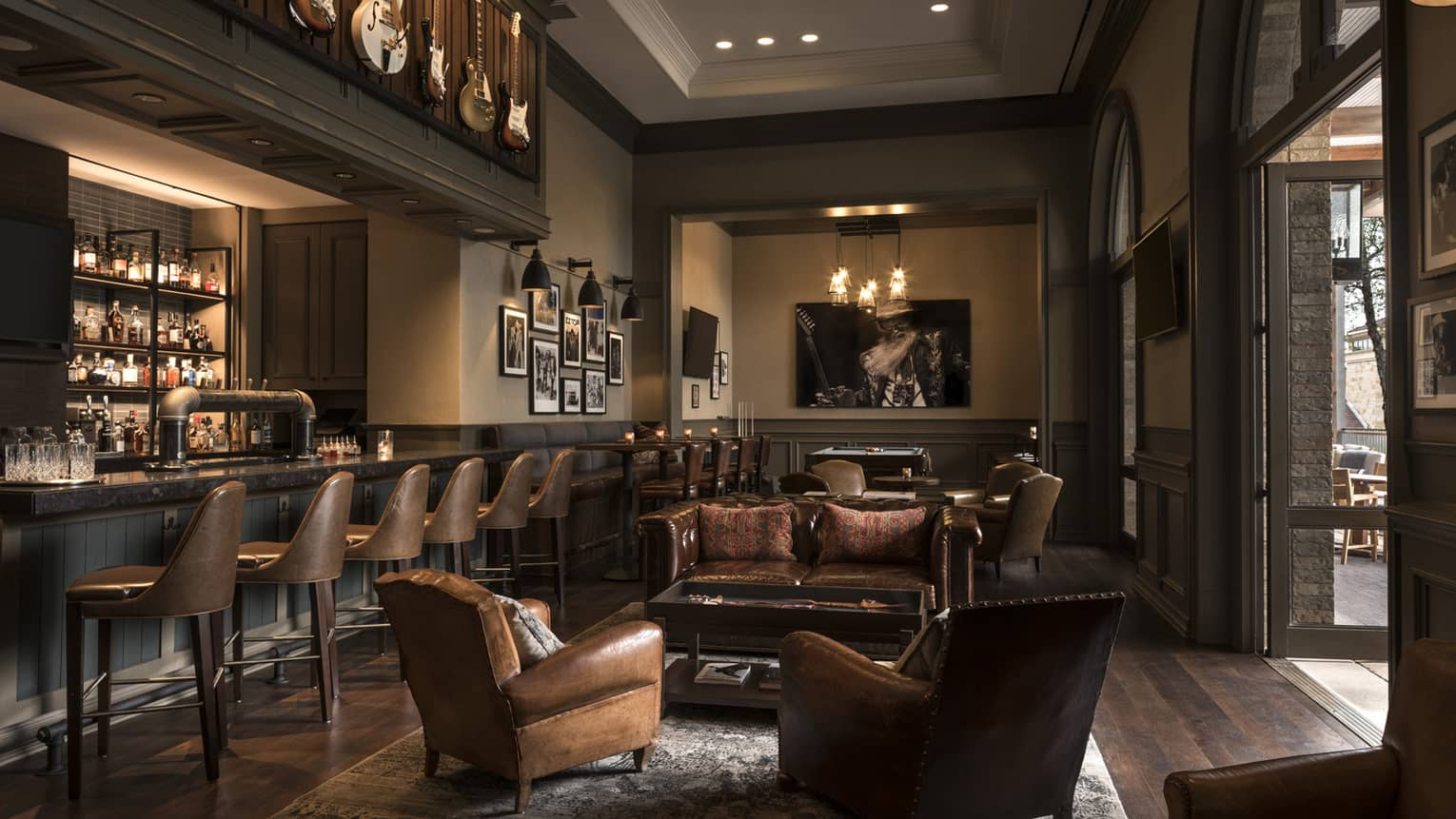 Indoor bar area, with dark wood floors, dark leather chairs and a bar counter