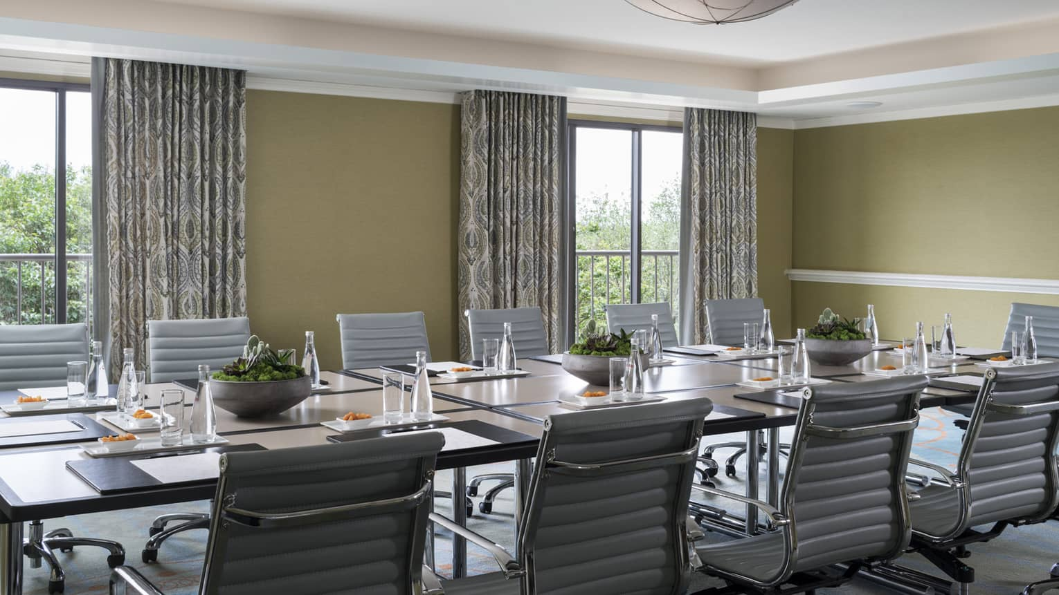 Chairs line long boardroom table in sunny meeting room with large windows, dome light on ceiling