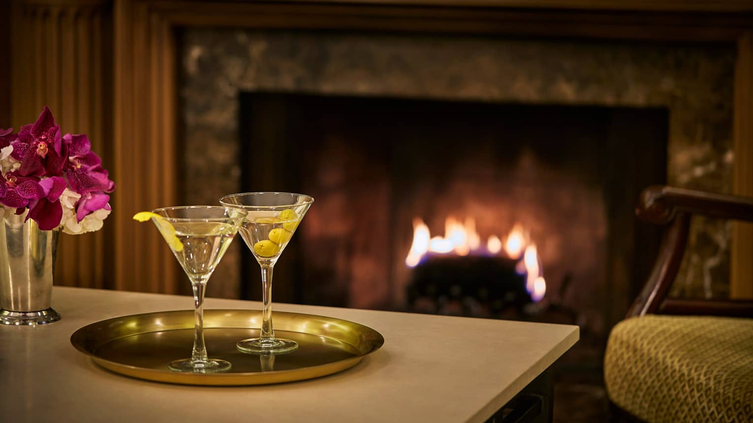 Tray with two martinis in front of roaring fireplace