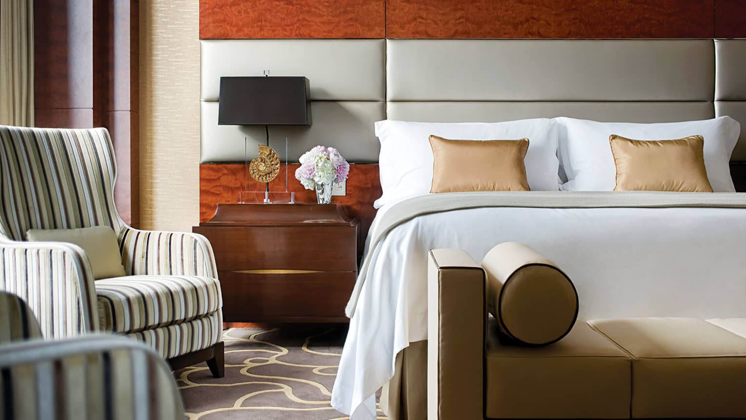 Two-bedroom Presidential Suite modern leather chaise at foot of bed, striped armchair by window
