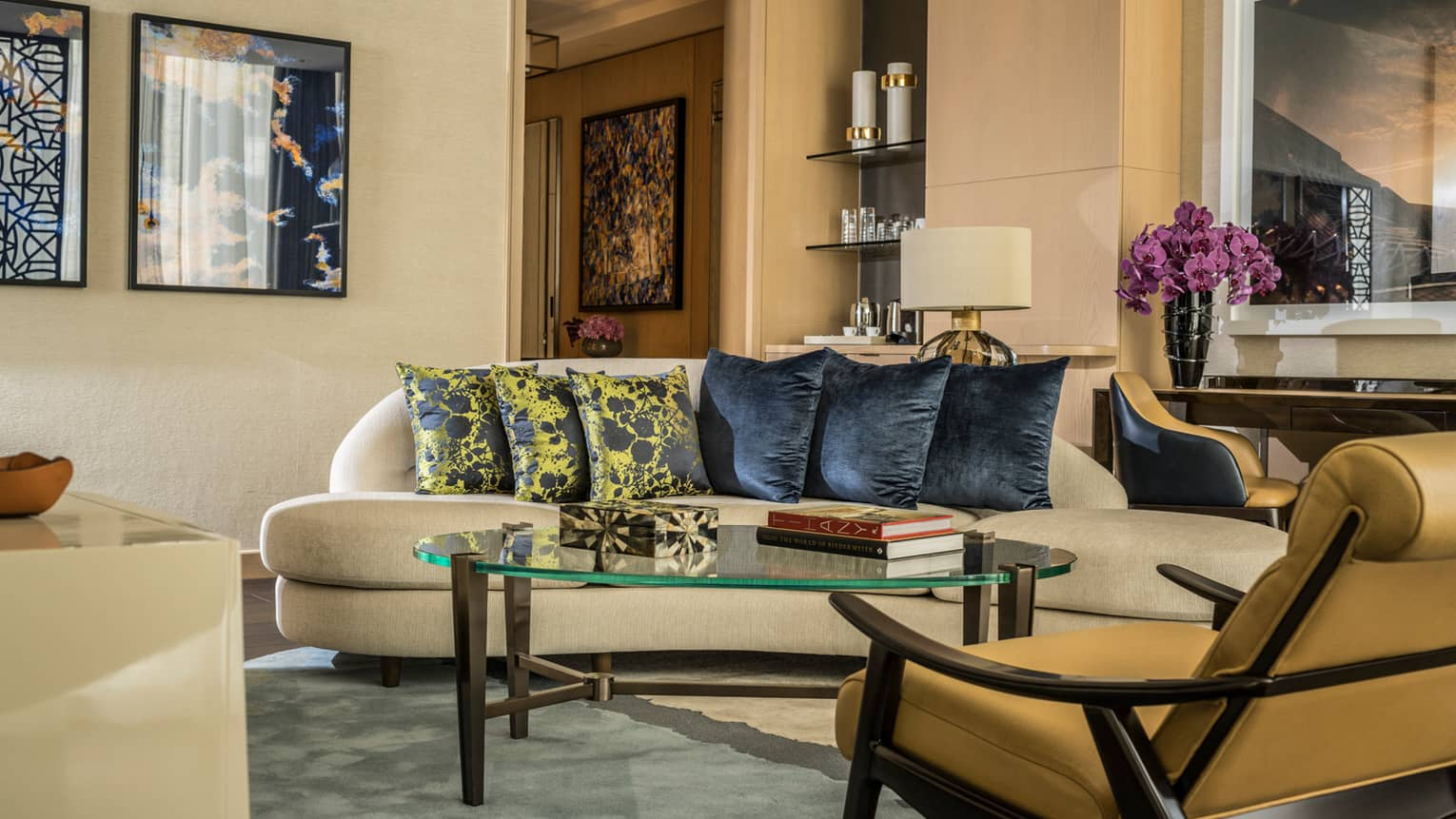 Four Seasons Executive Suite leather armchair, glass coffee table with books, sofa with six black and yellow accent pillows