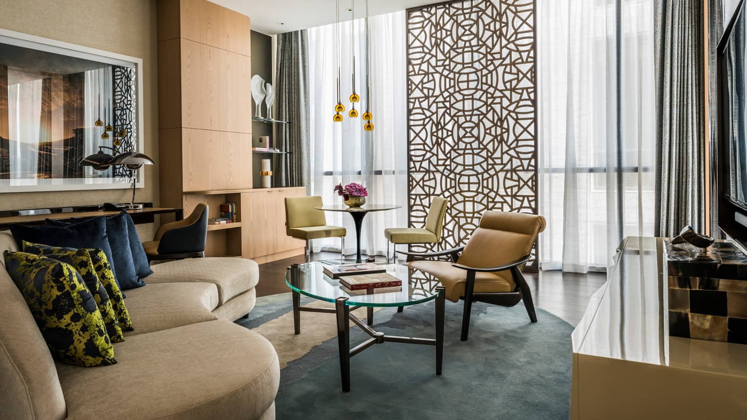 Four Seasons Executive Suite living room with curved sofa, accent pillows, glass coffee table, decorative screen