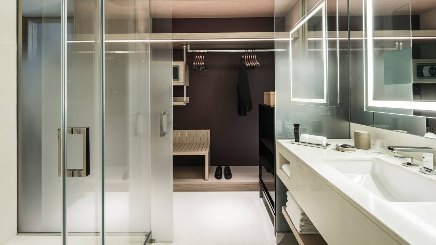 Premier Room bathroom with glass shower, white sink, large walk-in closet