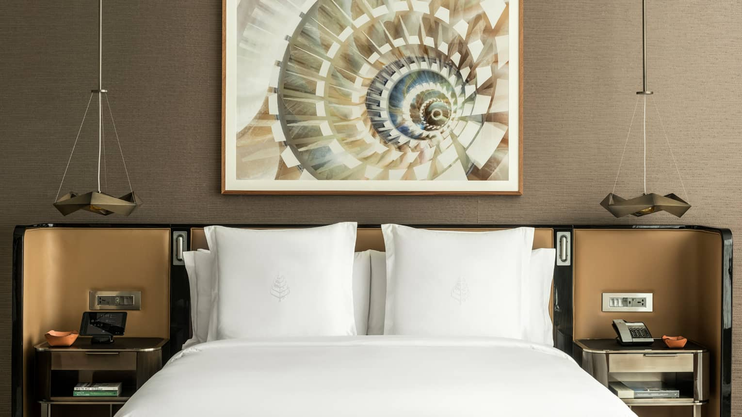 Top of bed with white linens, pillows against padded headboard and nightstands, art on wall