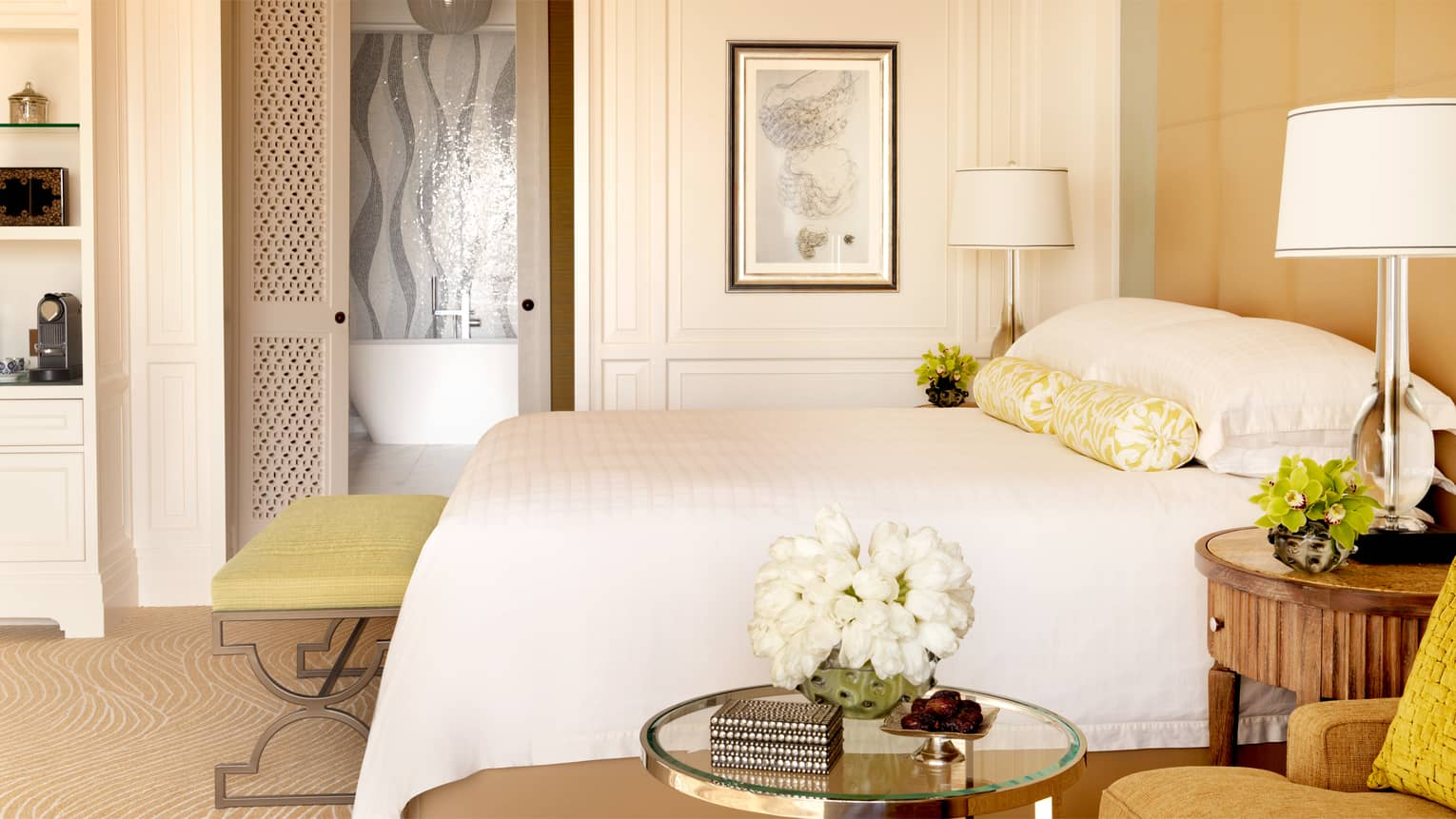 White bed with yellow bench in front of sliding door to bathroom with white freestanding tub