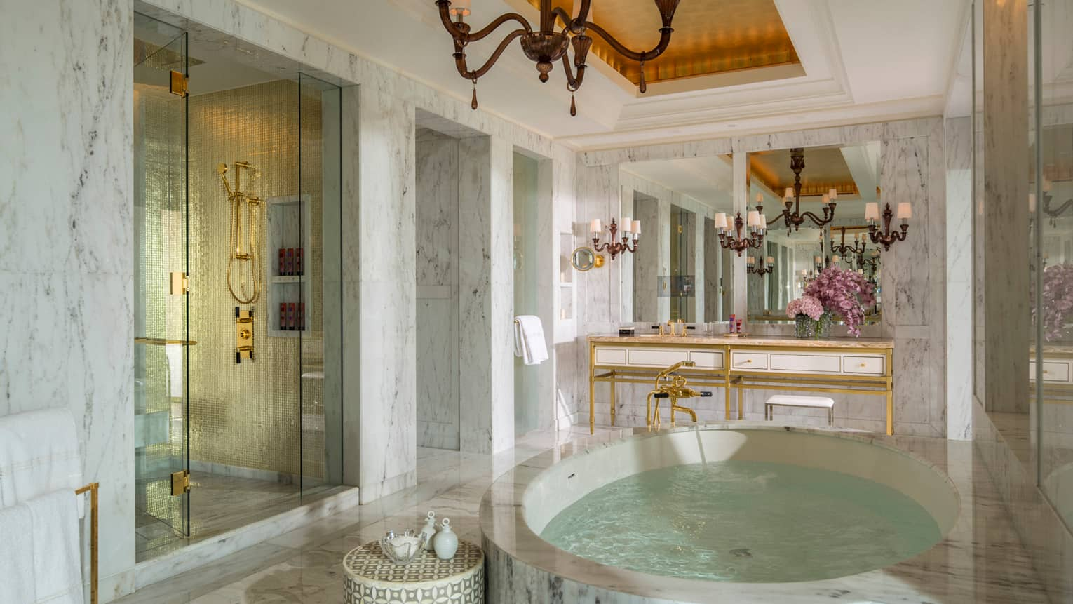 Royal Suite white marble master bathroom with circular spa tub, stand-up shower