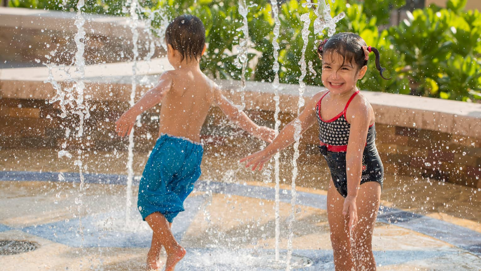 Young boy and girl in swimsuits run through water splash pad