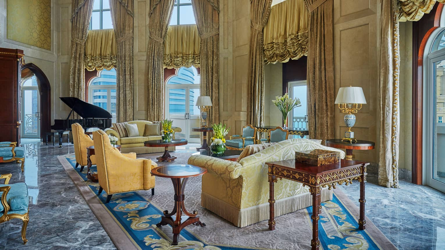 Royal Suite large living room with sweeping ceiling, blue-and-gold carpet, gold sofas and curtains