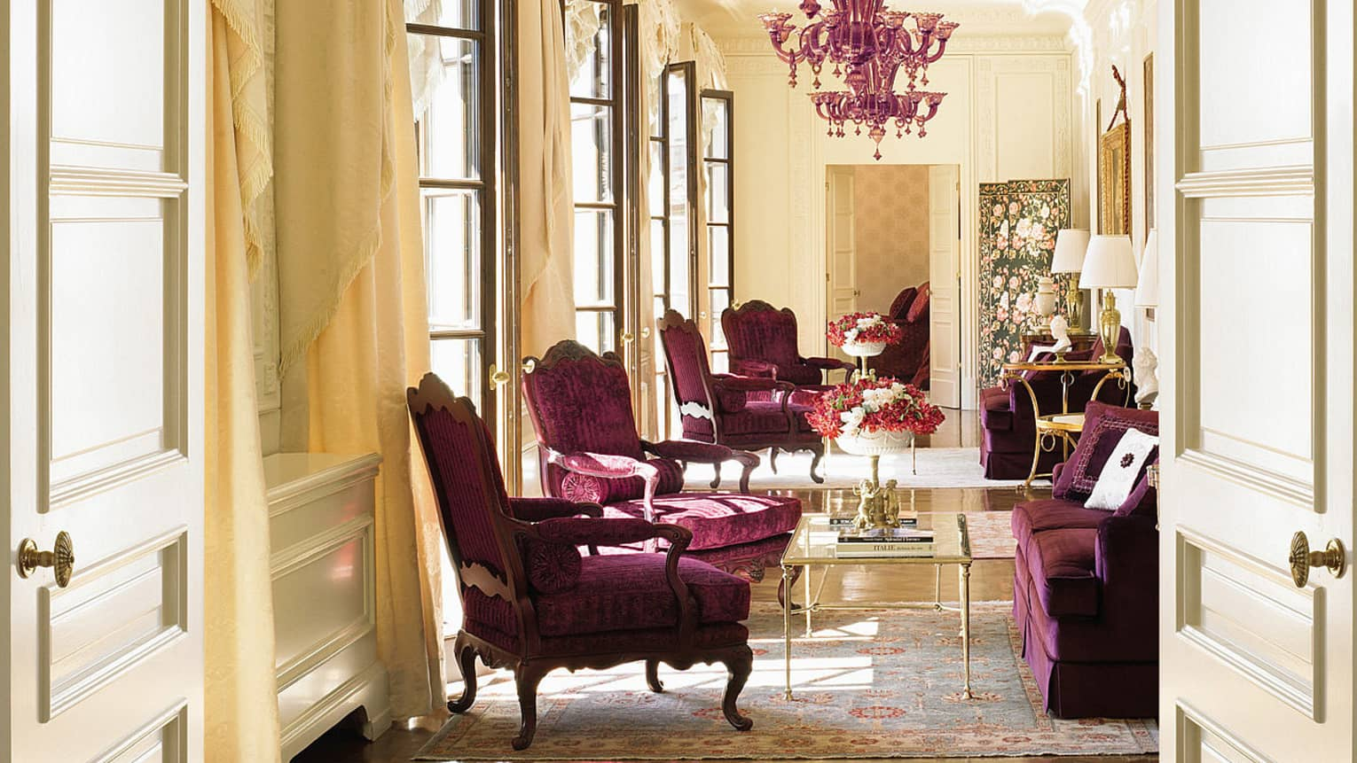 Sunny Presidential Suite purple velvet armchairs, loveseat under purple crystal chandelier