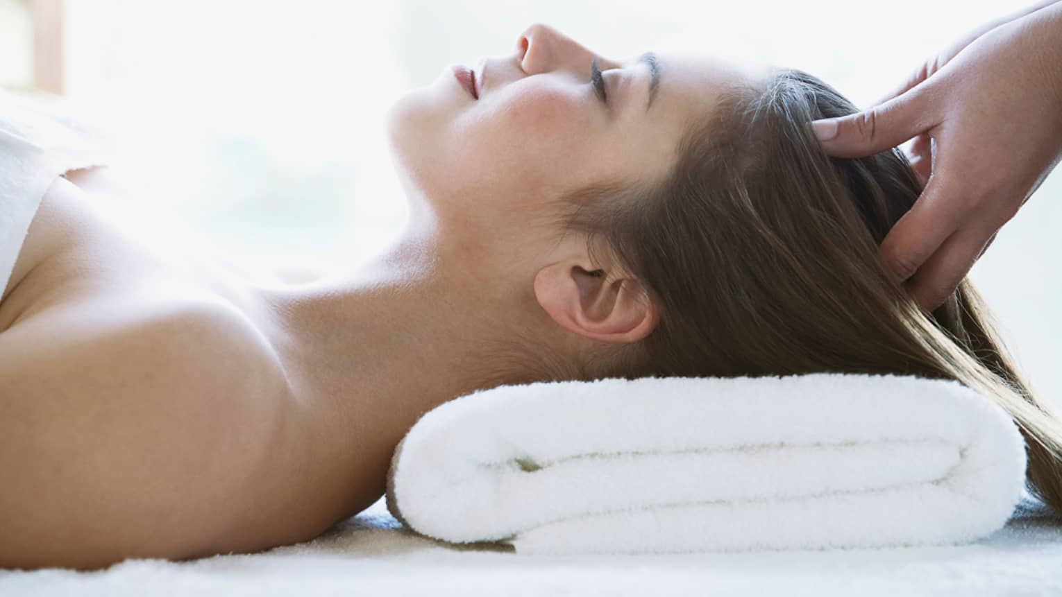 Woman lays on back with head on folded white towel, closes eyes as hands massage her scalp