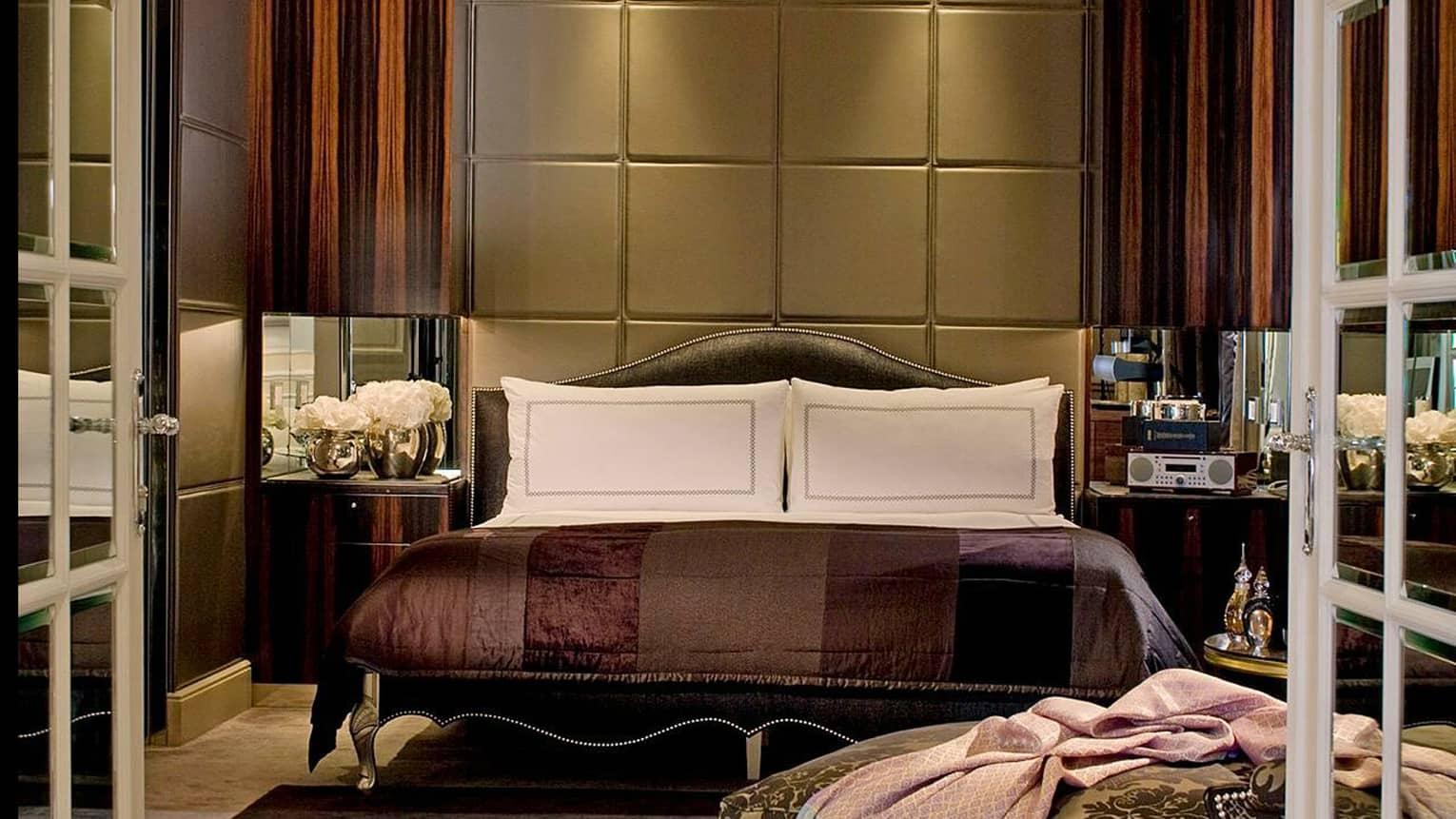 Dimly-lit hotel room, bed with deep brown and purple satin bedspread, tall fabric headboard and wood panel walls