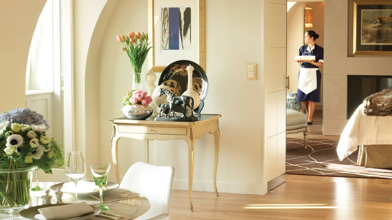 Presidential Suite Loft sunny table with fresh flowers, horse statue, vases, hotel staff walks by bed in background