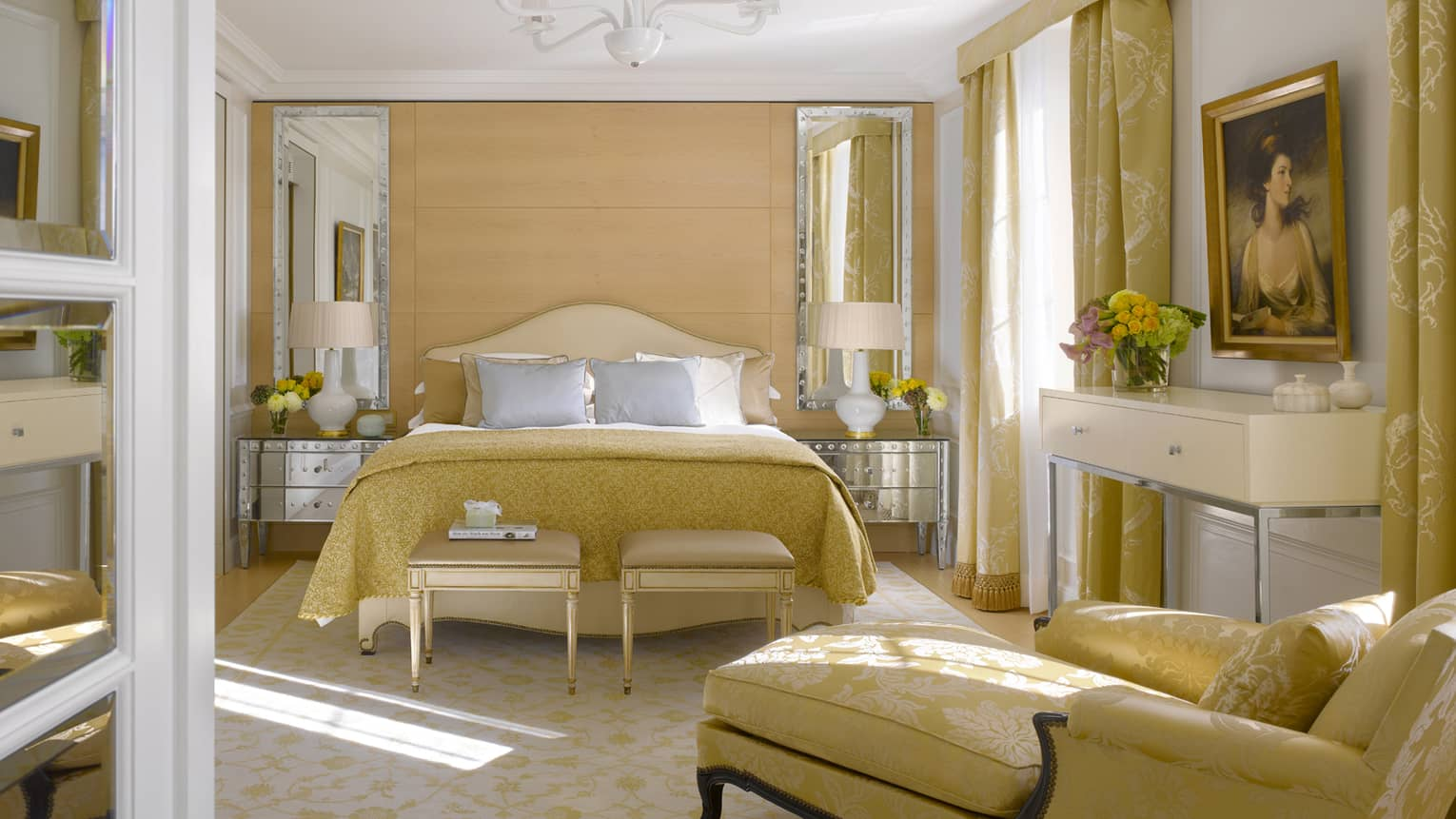 Bedroom with yellow-gold upholstery, chaise lounge and french doors