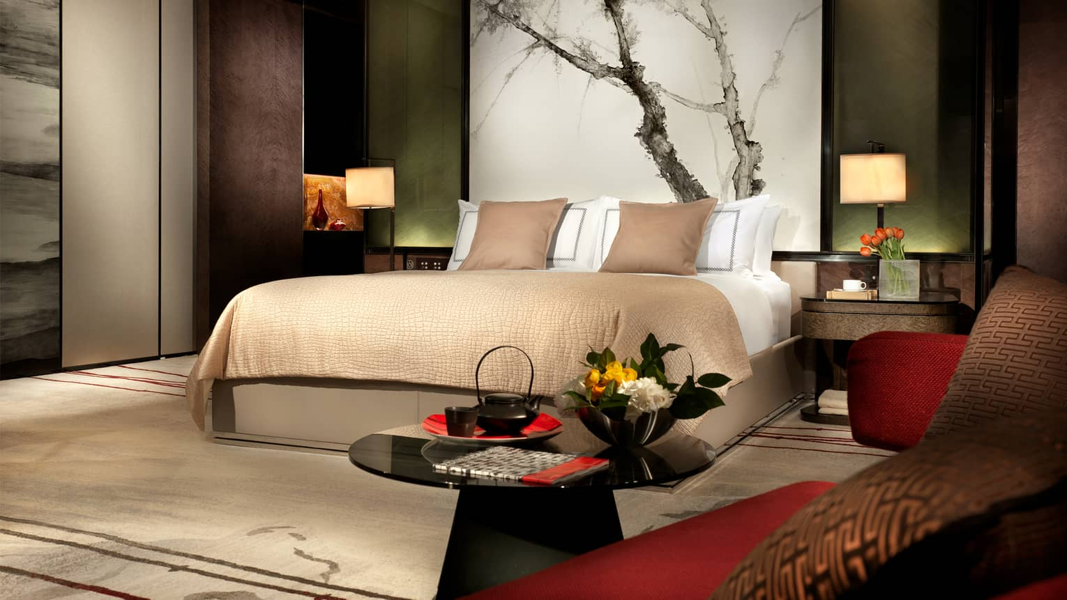 Hotel room platform bed with headboard painting of tree branches, deep brown, red and green decor