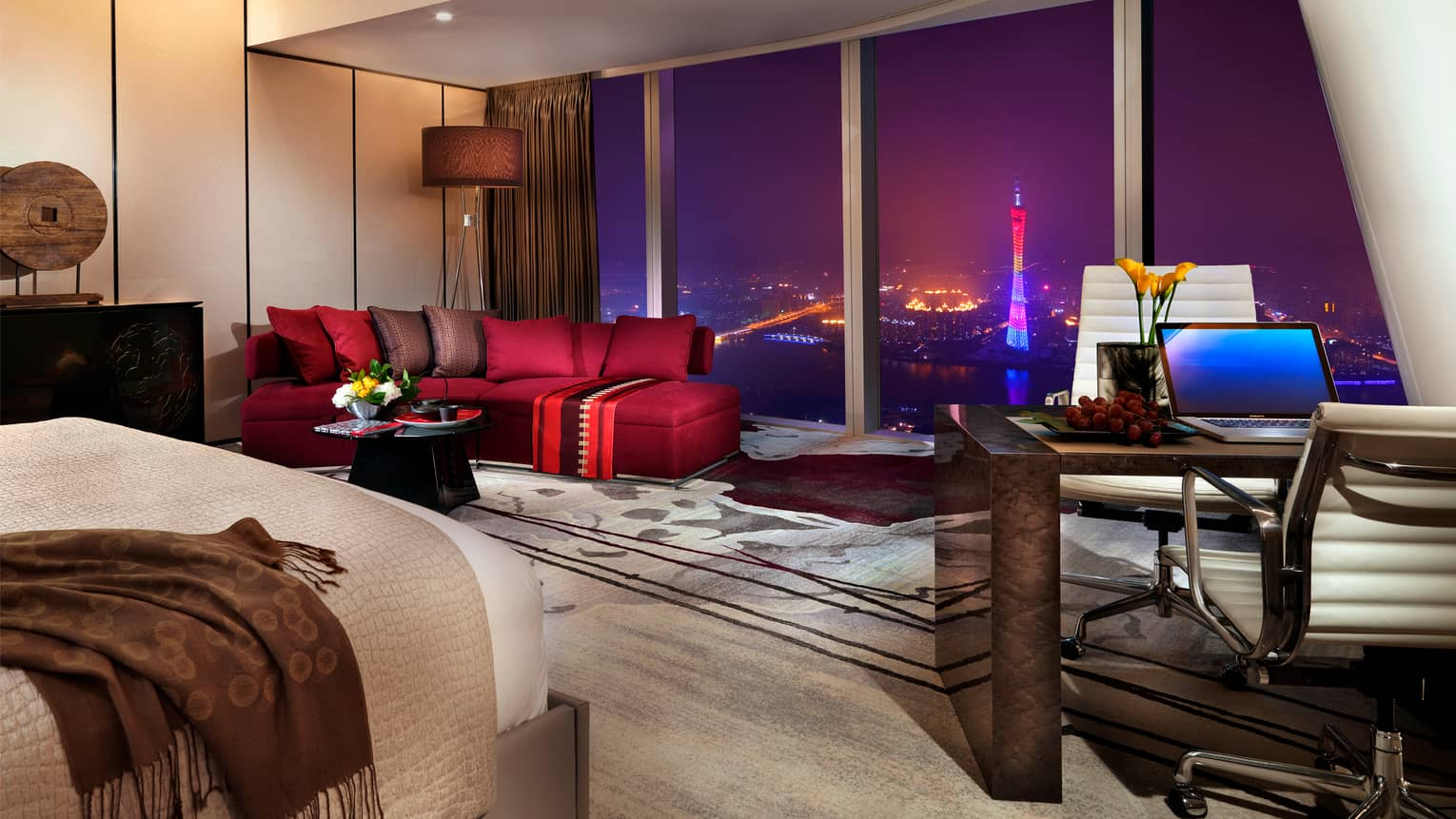 Floor-to-ceiling hotel room window at night with city view, beside stylish red sofa and area rug