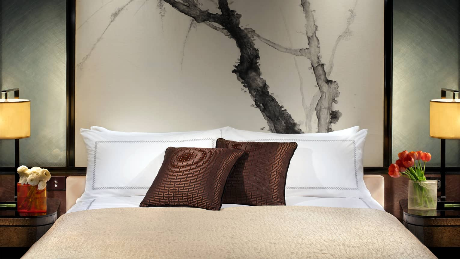 Close-up of bed with chocolate-brown accent pillows, tall headboard with black-and-white painting of branches