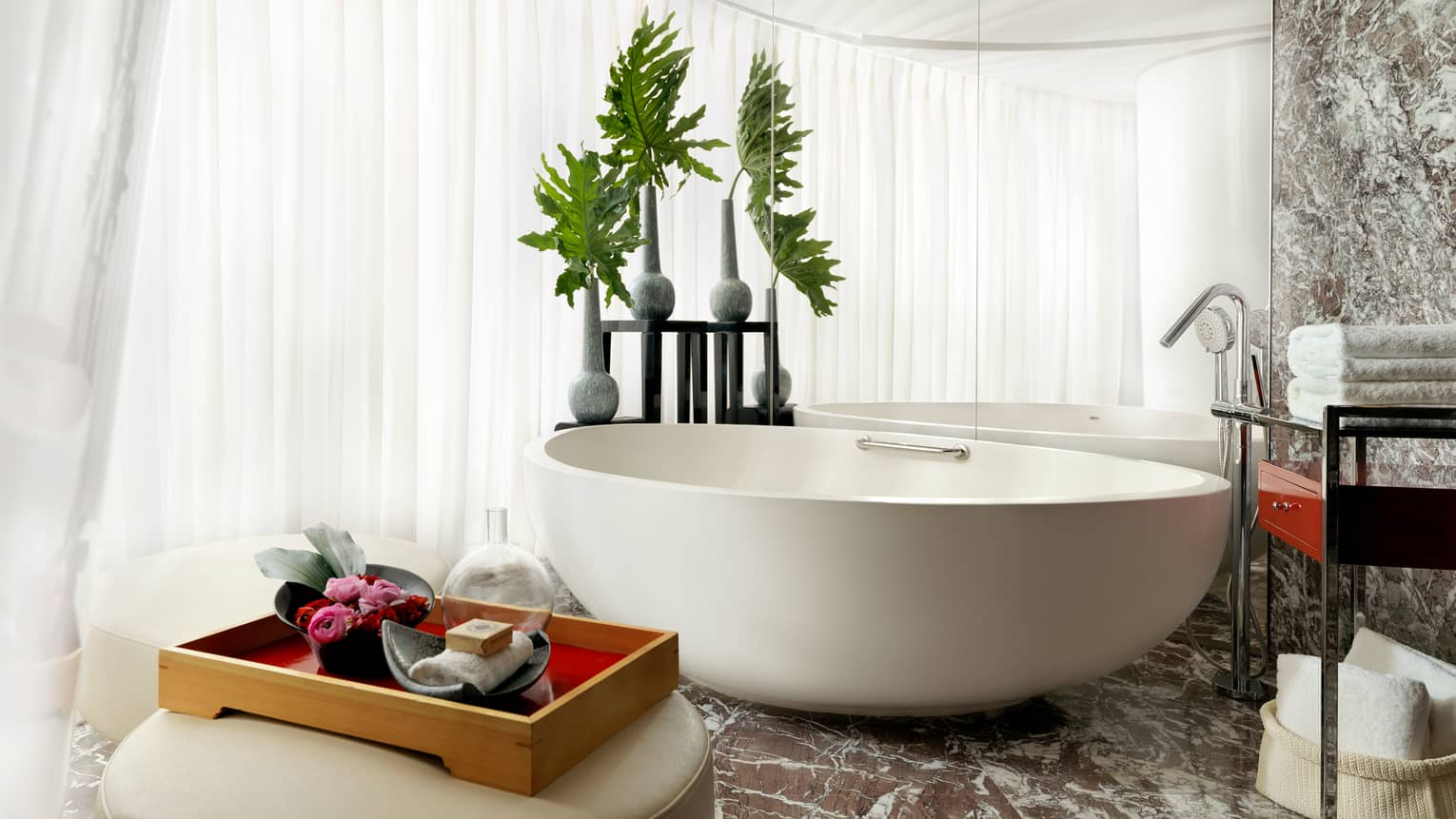 Free-standing white bathroom tub with modern vases holding decorative leaves, white stools with red tray