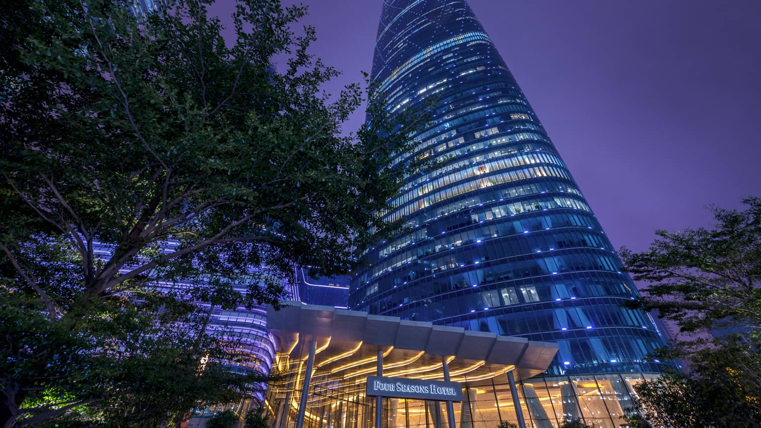 Four Seasons Hotel Guangzhou at night, high rise building with blue lights