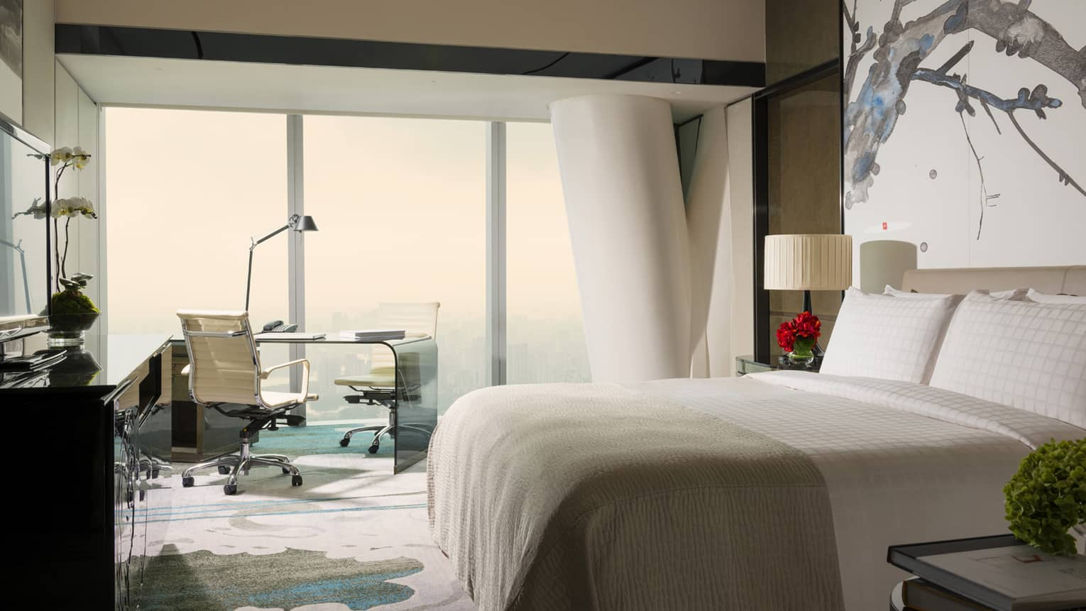 Tower Room with View bright decor with white bed, white and blue carpet and art, floor-to-ceiling window