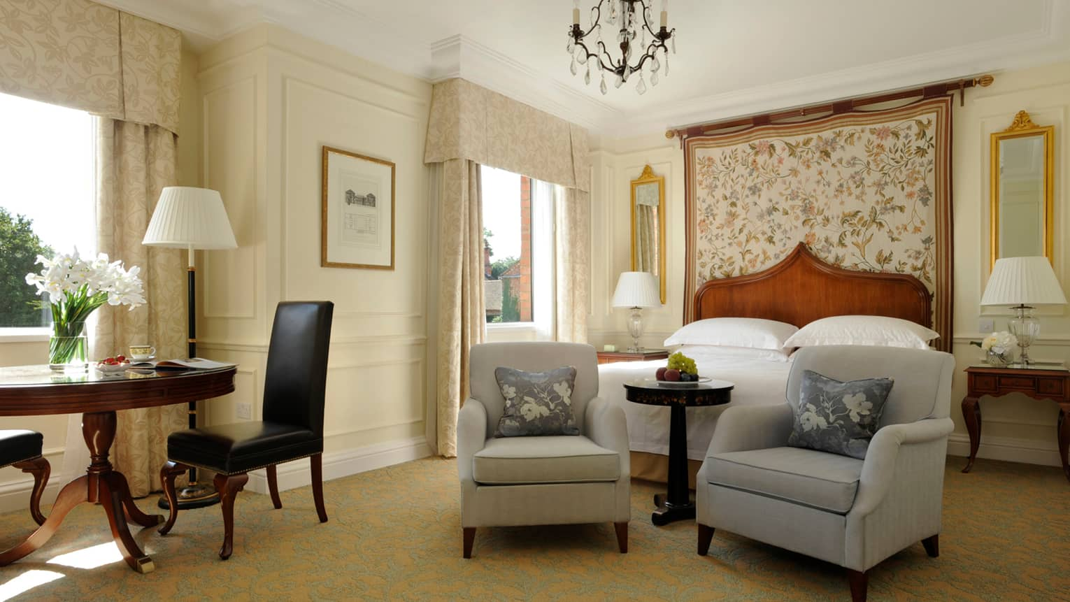 Heritage Room, two armchairs at foot of bed with floral headboard, desk by window