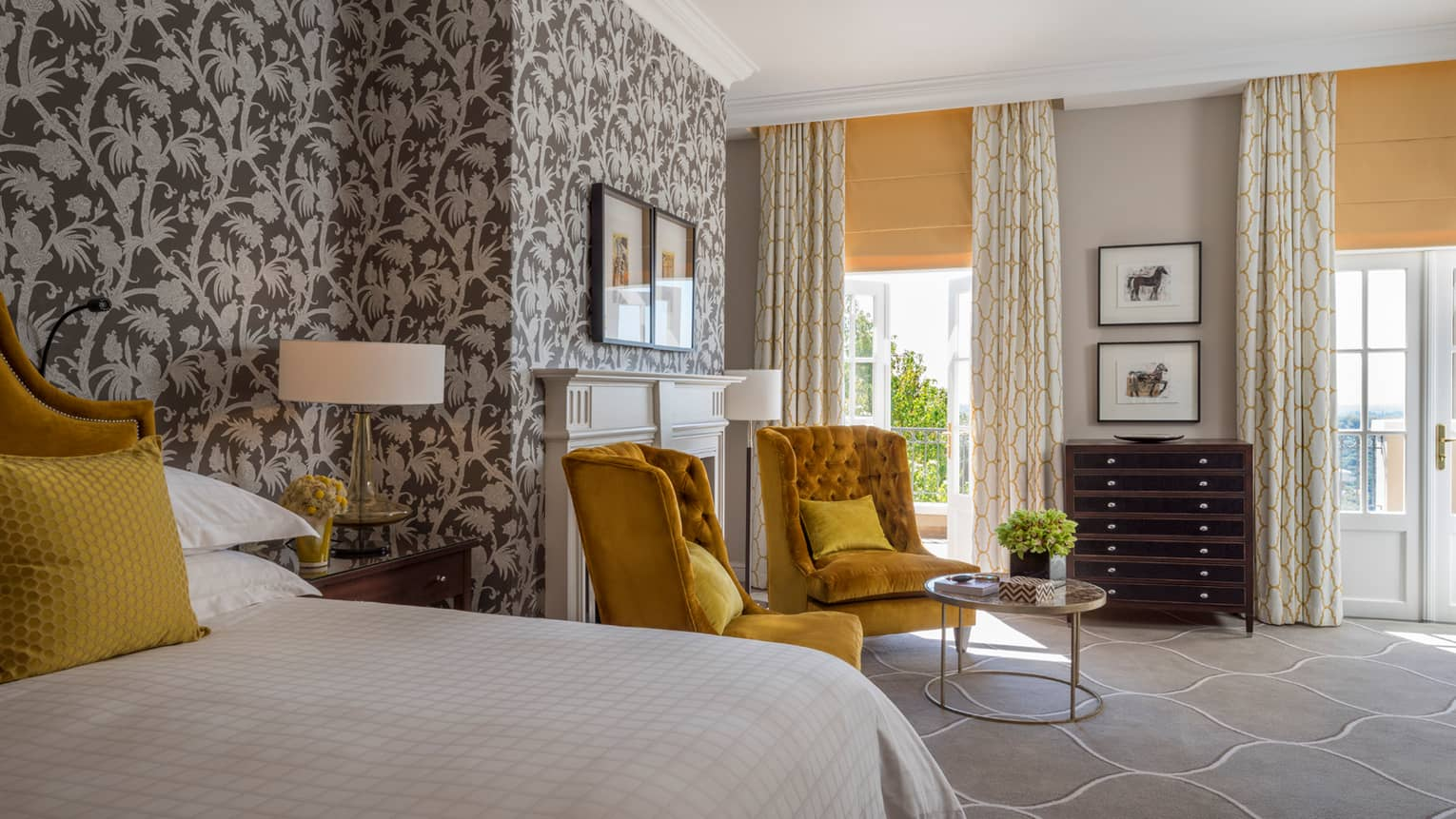 Royal Suite bed, two gold tufted armchairs around small glass table, tropical wallpaper