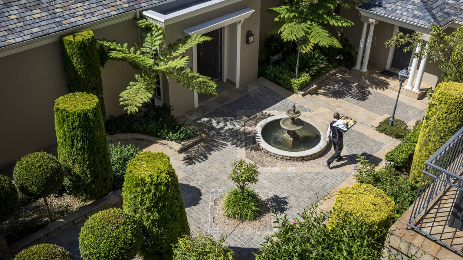 Aerial view of waiter carrying tray through brick courtyard with manicured green shrubs