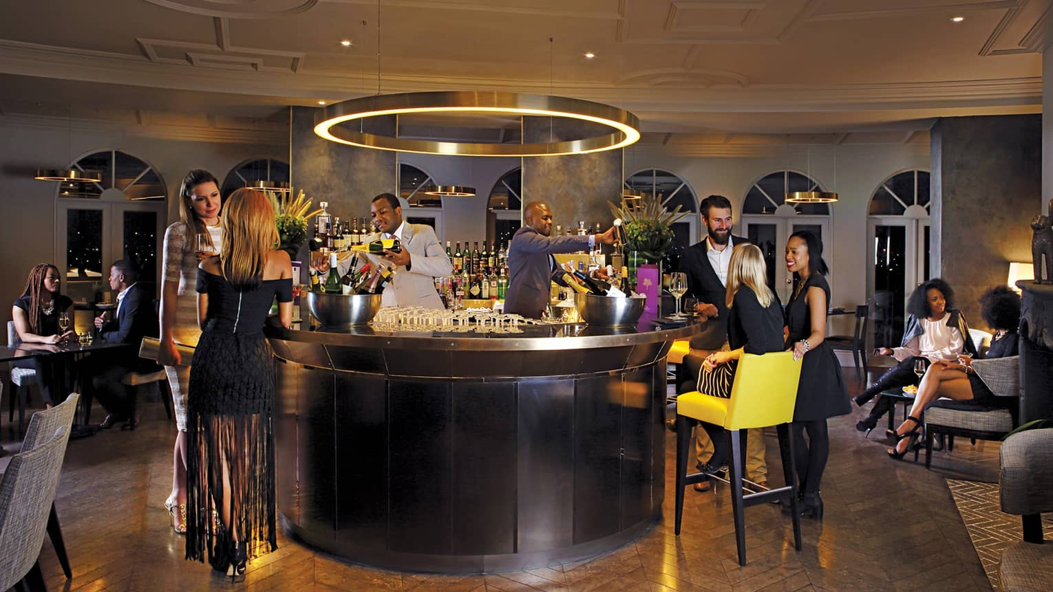 People in formal clothes socialize around small round bar with bartenders in Pre View restaurant