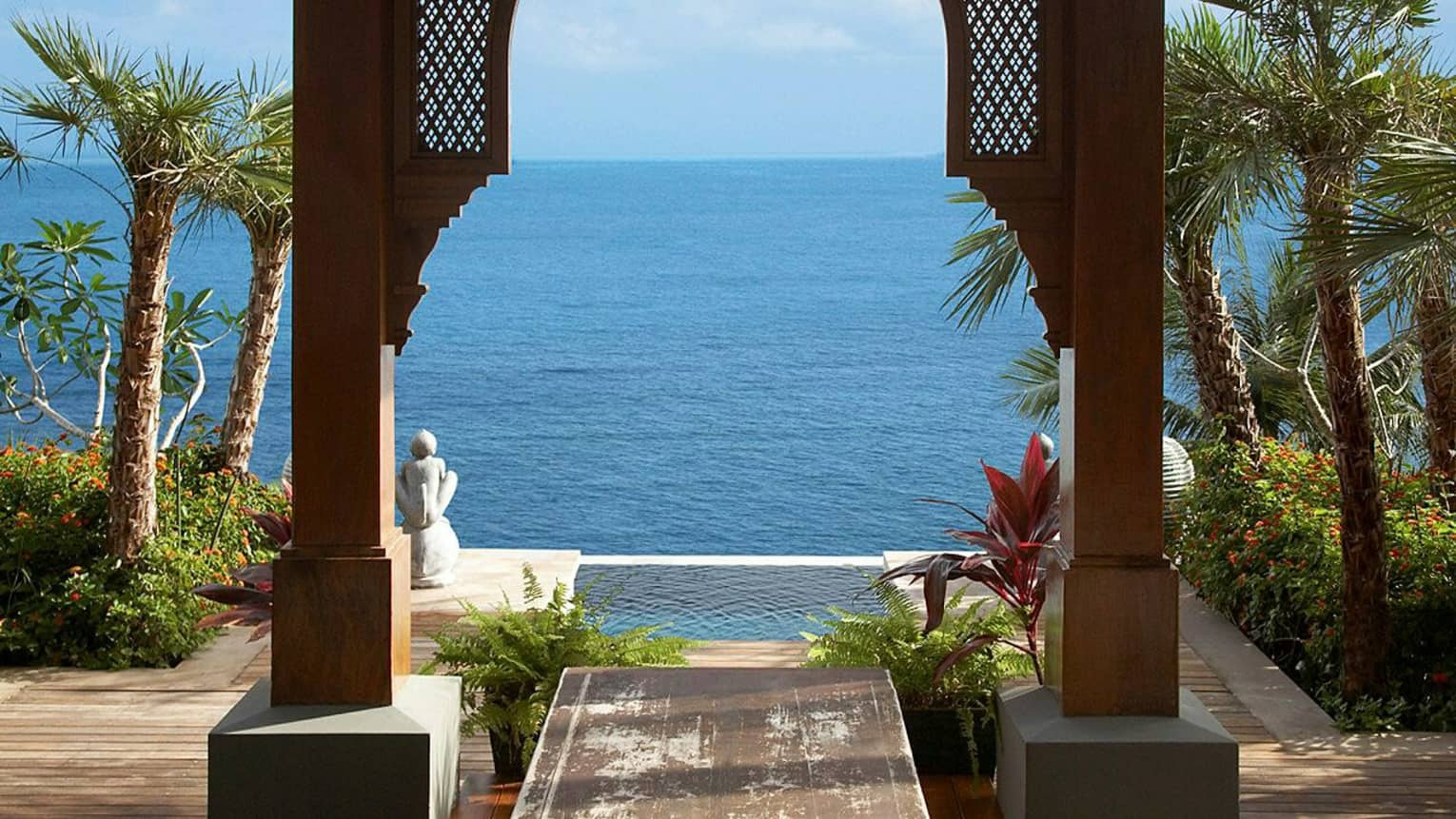 Wood archway, pool palms and ocean under blue sky