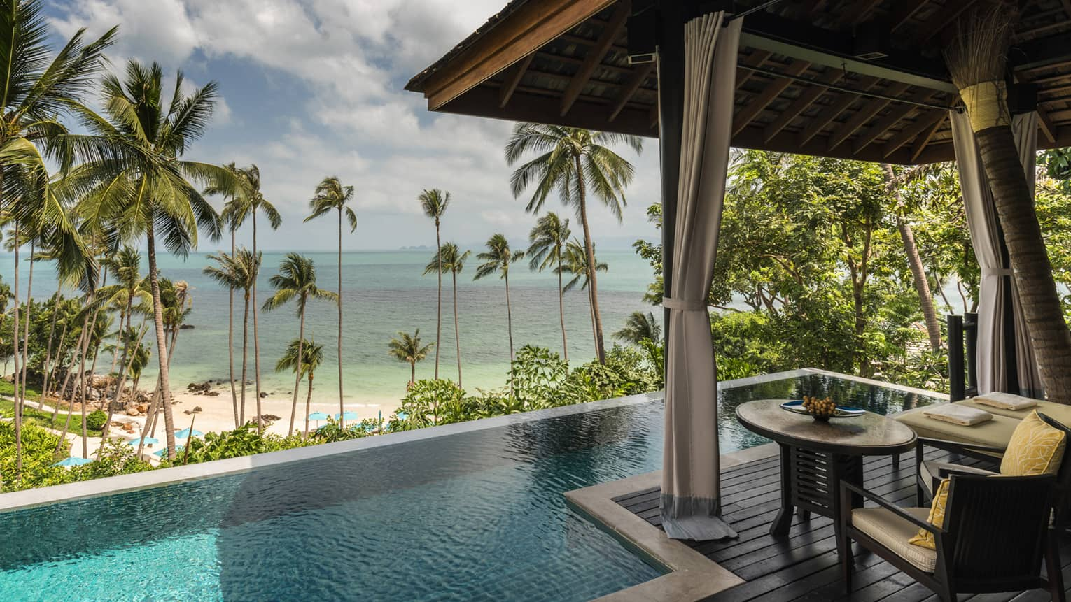 Beachfront Pool Villa small round table on patio by plunge swimming pool, beach and ocean view