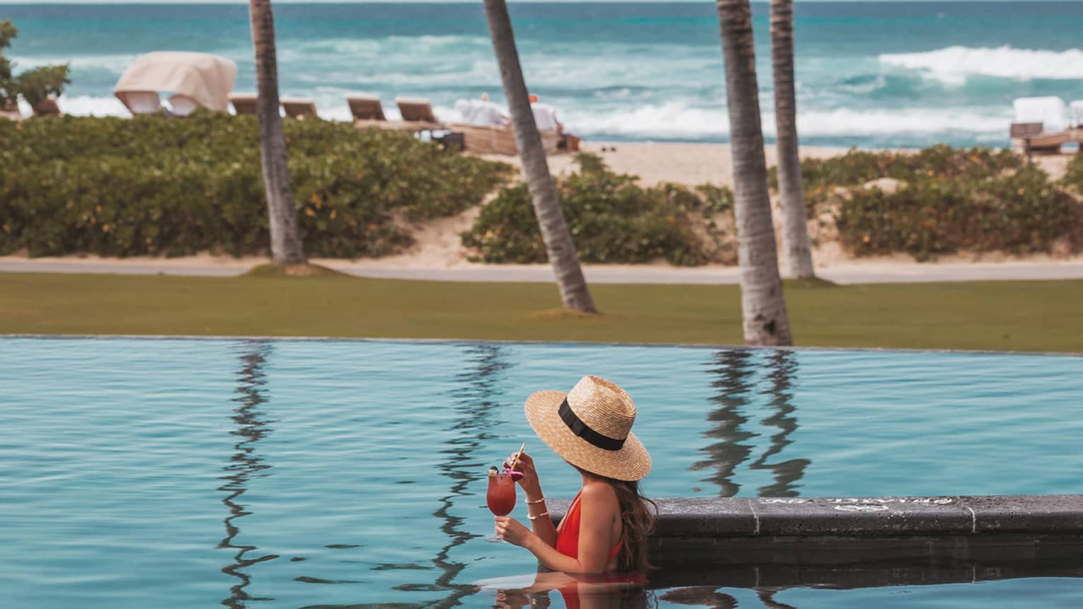 Side view of person in pool wearing straw sunhat and holding drink, ocean view