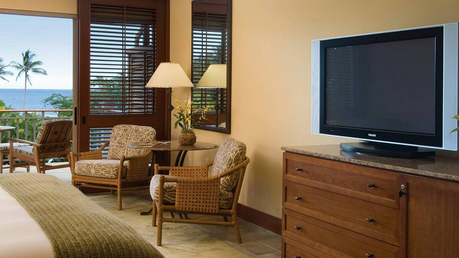 Oceanfront Room end of bed with folded wood blanket, dresser with TV, table and chairs by patio