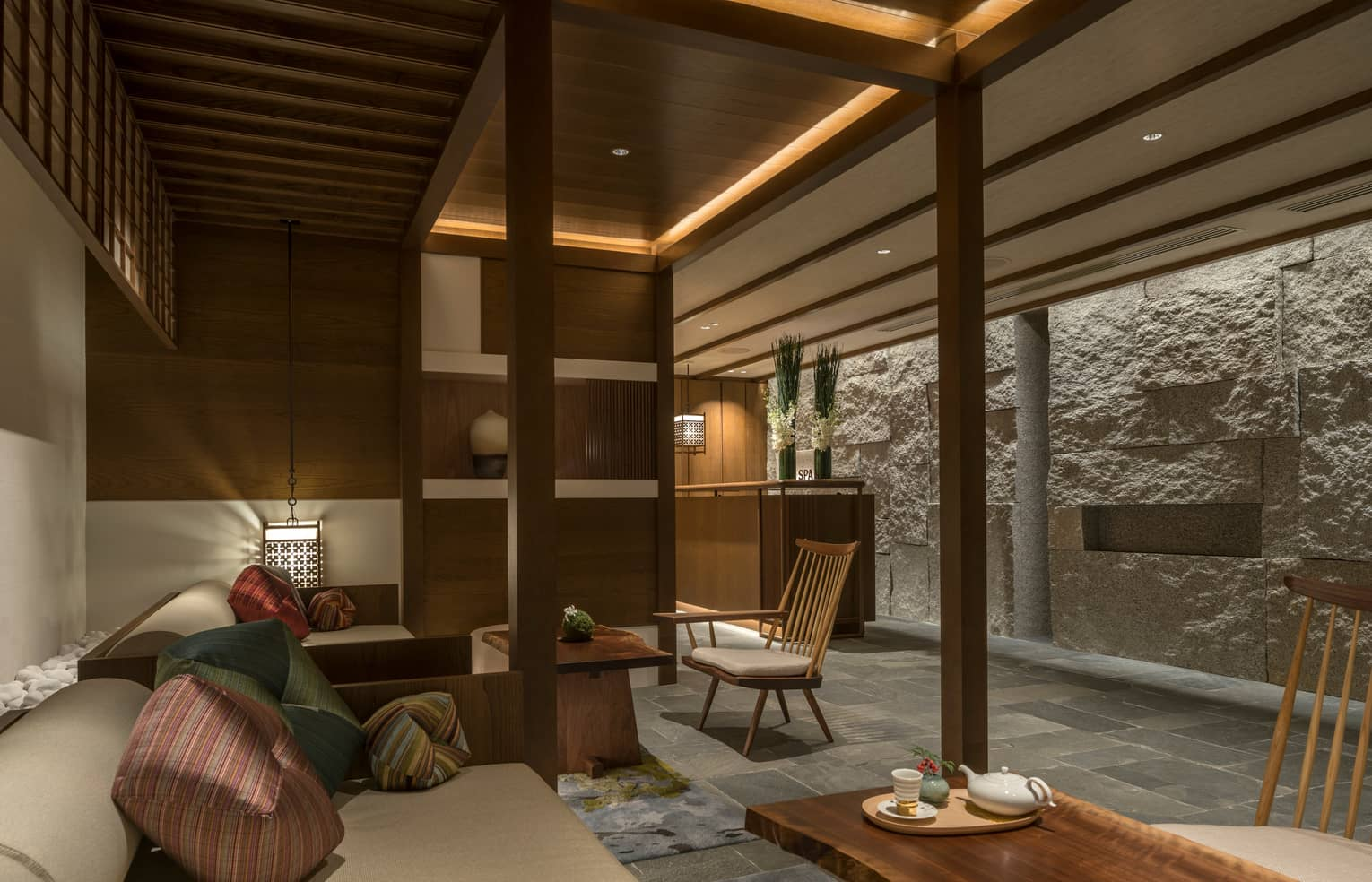 Spa lounge with plush bench, cushions, tea on table, lanterns, rock wall