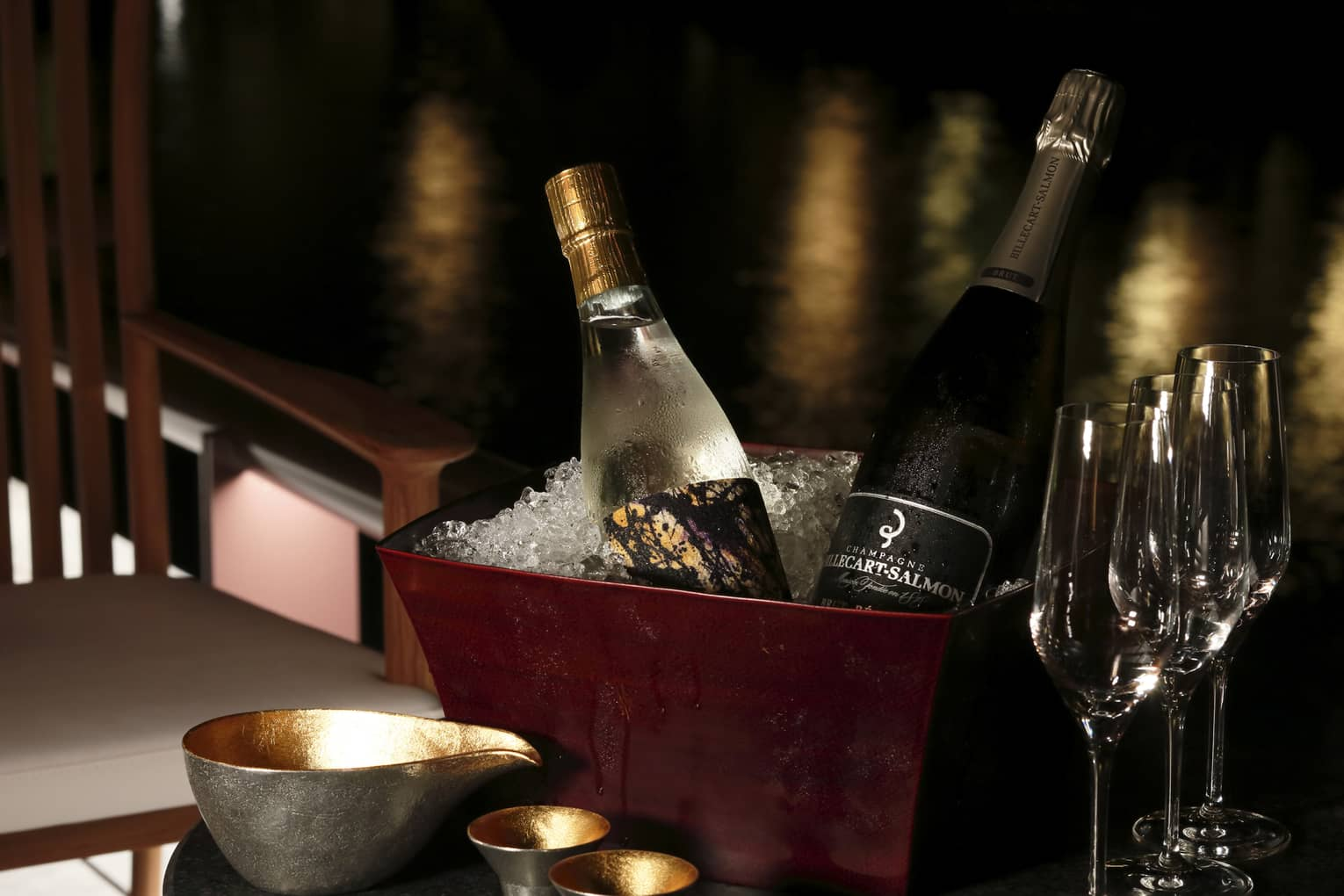 Bottles of sake and Champagne in brown ice bucket on table with glasses
