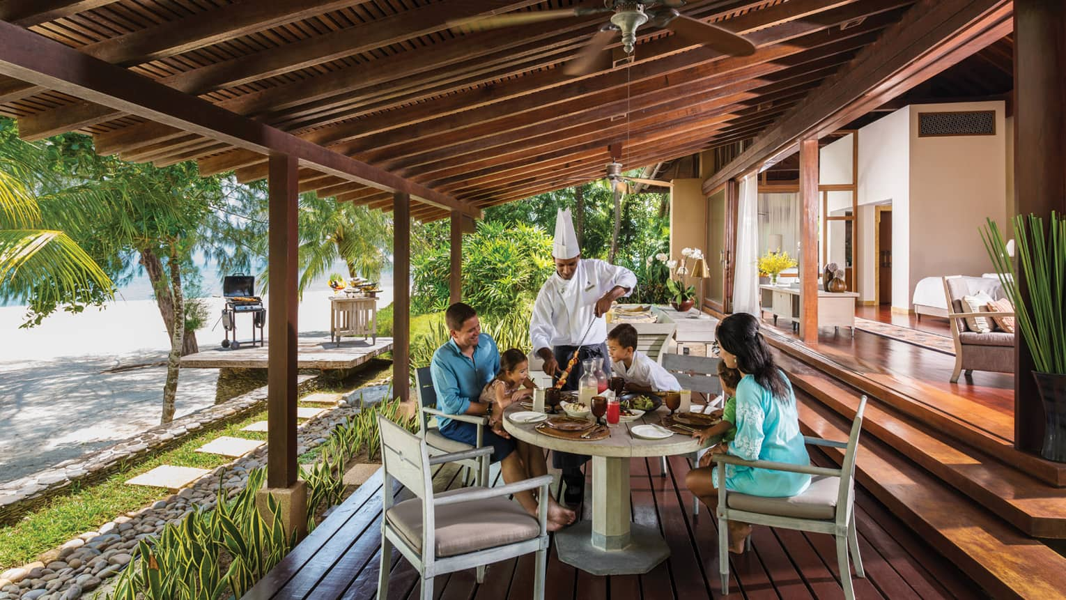 Chef in uniform presents meat skewer to family around table on Beach Villa patio