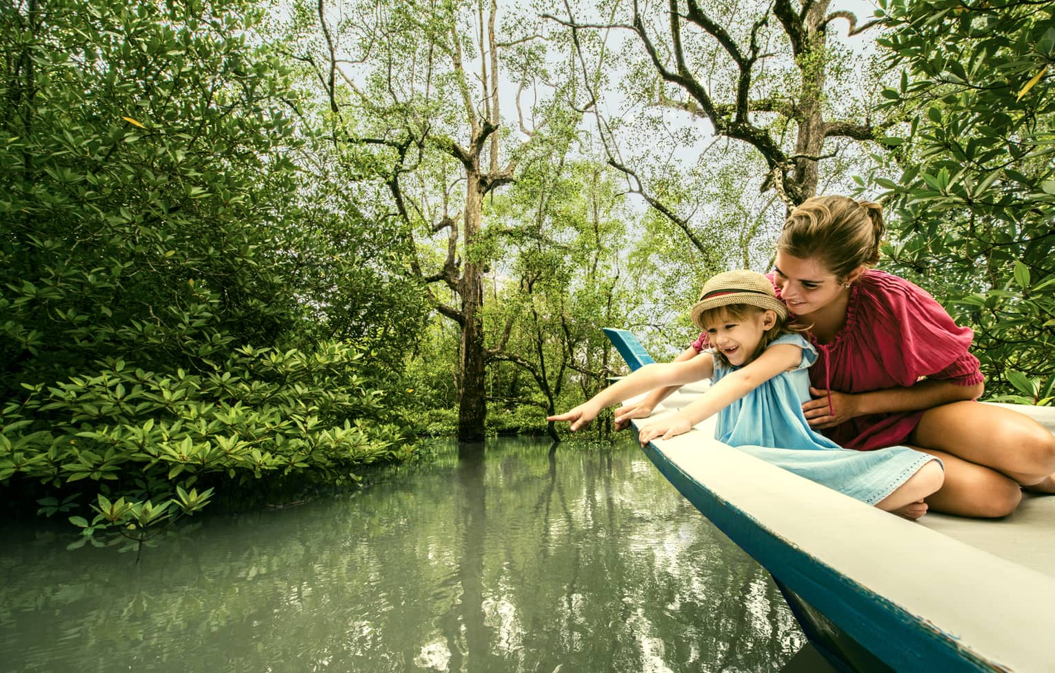 Mom, young daughter in back of wood canoe look into river