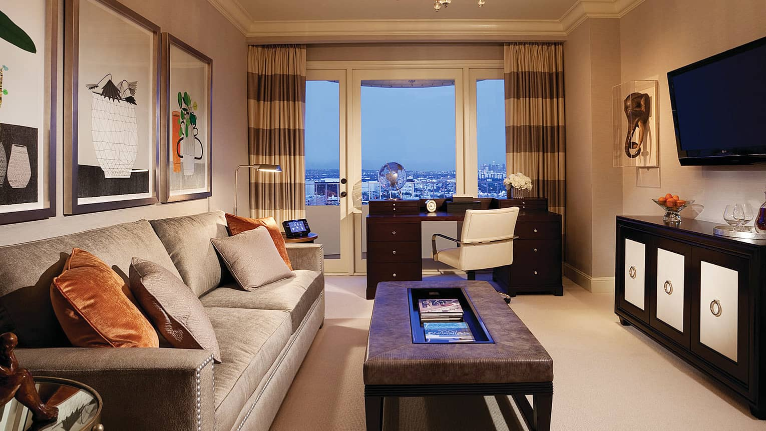 Hotel room living area with beige satin sofa, orange cushions, leather coffee table, desk at window overlooking city