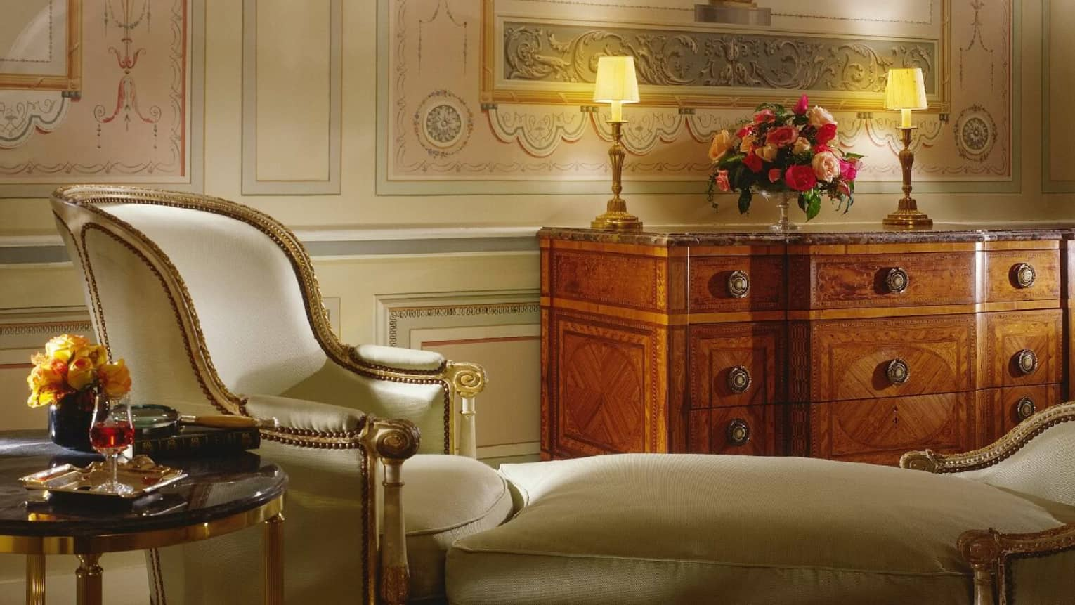 Close-up of Presidential Suite antique-style satin armchair with gold wood trim, ottoman, table with wine and roses
