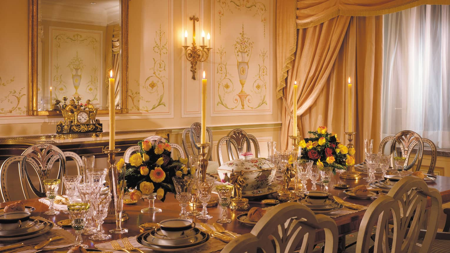 Presidential Suite elegant private dining table with tall candles, crystal glasses, antique dishes, wall panels