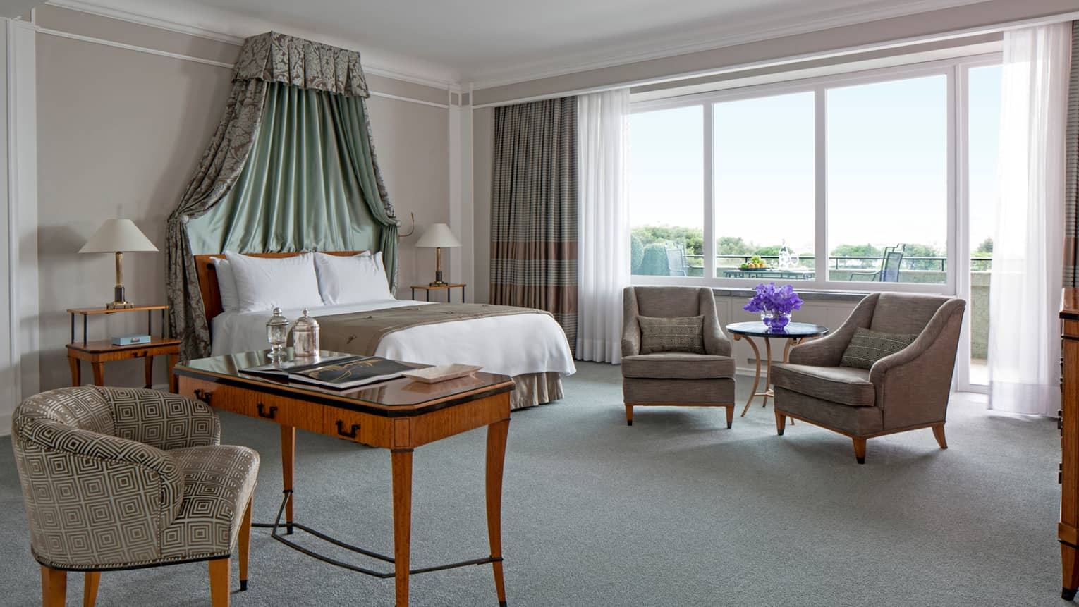 Central One-Bedroom Suite large sunny bedroom, bed with green ruffle canopy, writing desk and chair, window