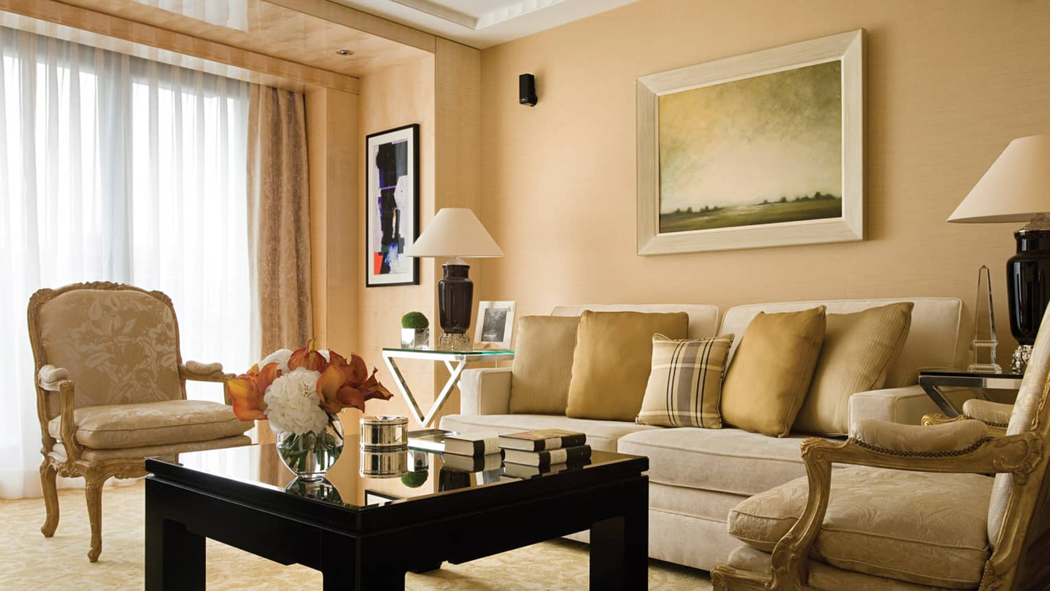 One-bedroom Suite living room with gold accent chairs, flowers and books on black coffee table