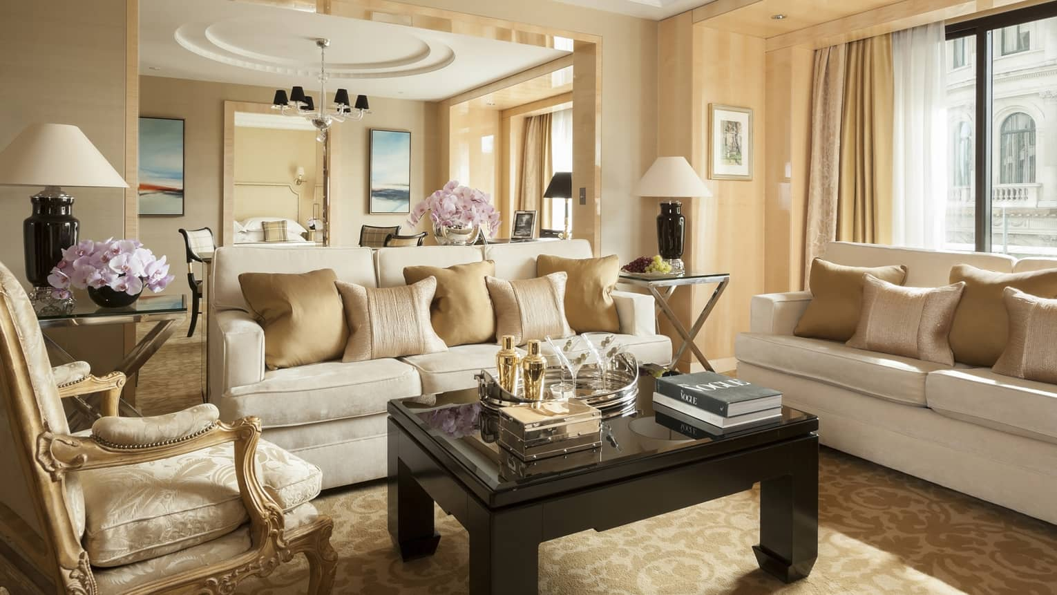 Grand One-Bedroom Suite elegant sofas, gold accent chairs under tall ceilings, dining room in background