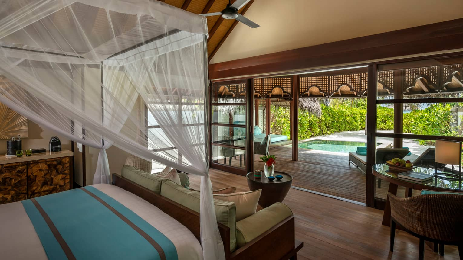 Beach bungalow canopy bed and sofa in front of open-air wall leading to deck and private plunge pool